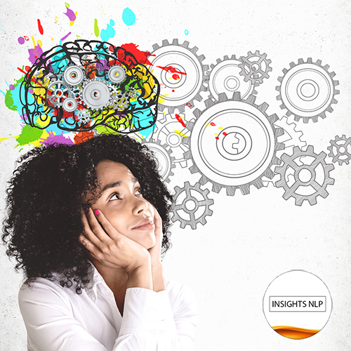 Smiling young African American woman in white shirt looking at colorful brain sketch with gears drawn on concrete wall. Concept of brainstorming